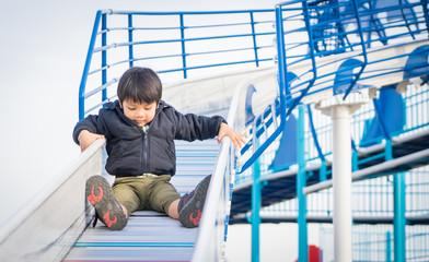 Japanese Boy Sliding down on a Slider playground