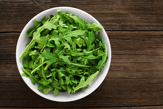 Bowl with fresh green salad arugula on a wooden background