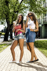 Two attractive women eating ice cream in the street at summer.