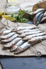 fresh sardines raw fish with coarse salt and thyme on brown pape