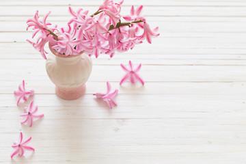 hyacinths in vase on white wooden planks