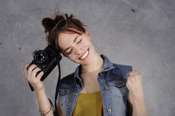 Funny young and trendy hipster girl with photo camera with emotions
