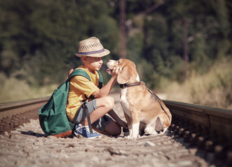 Fototapete - Little boy with his dog sitting on the railway