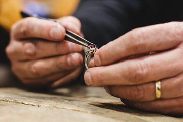 Close-up of a jeweler mounting a gemstone onto a ring