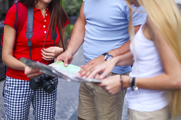 Three tourist looking at map in the street