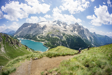 Man and woman riding mountain bikes along trail, Dolomites, Italy