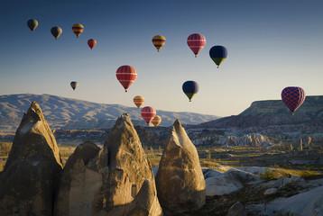 Hot air balloons at sunrise flying over Cappadocia, Goreme, Turkey