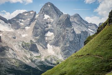 Man and woman mountain biking along trail, Dolomite moiuntains near Marmolada Glacier, italy