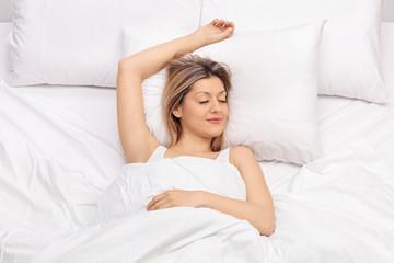 Joyful young woman sleeping on a bed