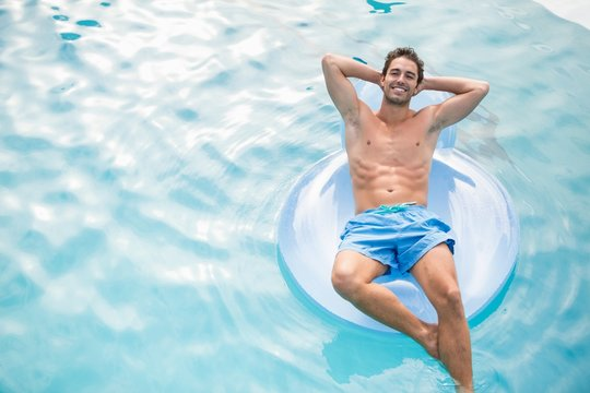 Shirtless man relaxing on inflatable ring