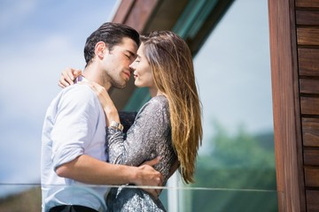 Romantic young couple kissing in balcony