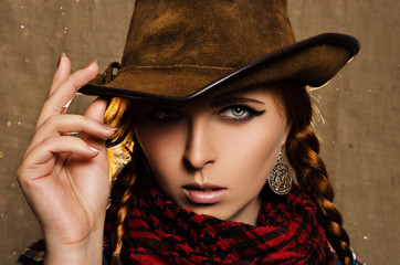 portrait of a beautiful young red-haired girl in a cowboy hat