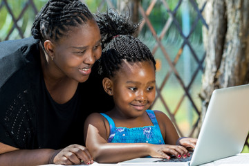 African mother and child looking at laptop outdoors.