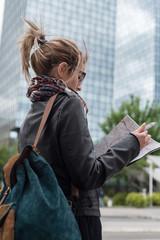woman looking at map near skyscraper