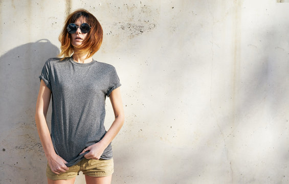 attractive young woman wearing in a gray blank t-shirt posing on a background of a concrete wall in the rays of the setting sun