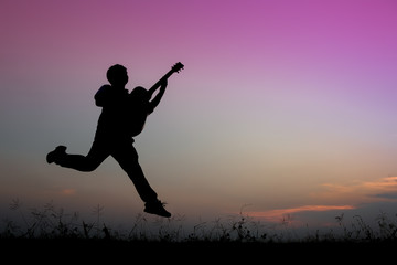 musician playing guitar against the background of sunset