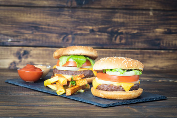 Two cheeseburgers with fries on slate plate
