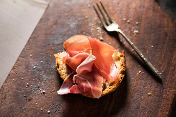 Ham with slice of bread on wooden board
