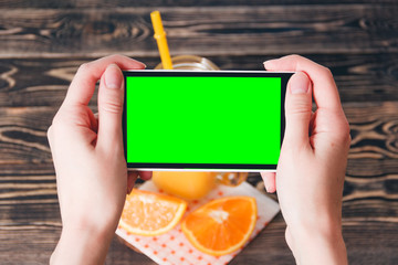 Hands Taking Photo of Oranges. Green Screen. Technology Concept