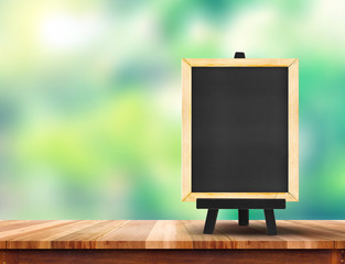 Blank blackboard on wood table top with sun and blur green tree