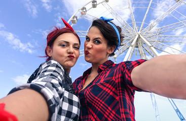 Pin up best friends taking selfie in front of ferris wheel