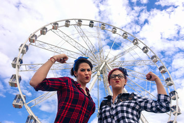 Pin up friends making funny gym position in front of ferris wheel