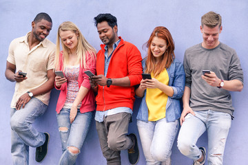 Cheerful young friends looking smart phone
