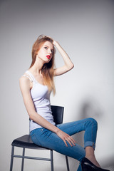 Awesome caucasian attractive sexy professional female model with blond hair posing in studio wearing white shirt and black ragged jeans, sitting on chair, isolated on white background