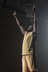 Portrait of basketball player throwing arms for the victory