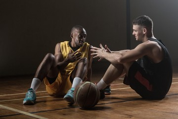 Basketball players sitting on floor talking together