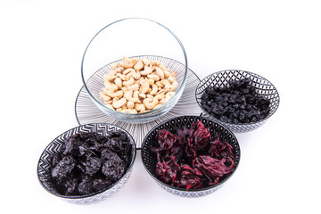 Bowls with dried blueberries, plums, hibiscus and cashews