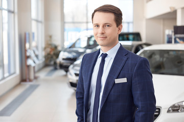 Smiling salesman in new car showroom