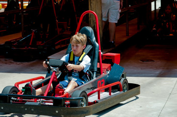 Cute little boy on red go cart.