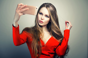 Beautiful woman in red dress with perfect cute face and blue eyes taking selfie with smartphone in studio.
