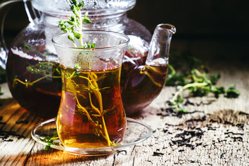 Middle East Black tea with thyme, ethnic glass and glass teapot,