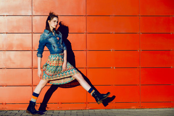 Young teenager girl posing, going, runs near urban red wall background in skirt and jeans jacket on the sunset.
