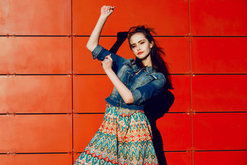 Young teenager girl having fun, posing and smiling near red wall background in skirt and jeans jacket on the sunset.