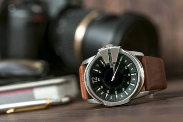 Closeup toned shot of male watches lying on table against photog