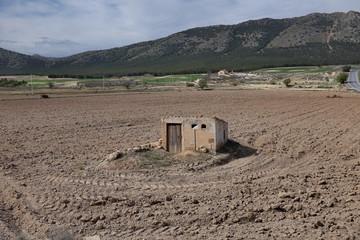 Petite cabane au milieu d'un champ labouré Wall mural