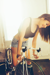 Young woman on white retro bicycle in studio