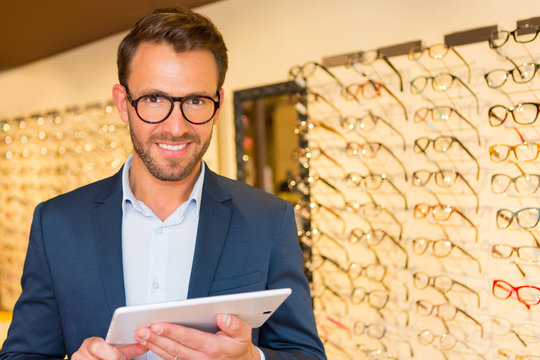 Attractive optician working with tablet in his glasses shop