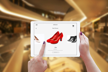 Woman online shopping with tablet. Holding device and choose red shoes. Shopping center in the background.