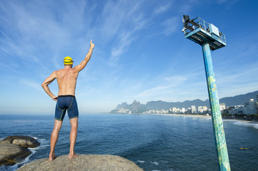 Athlete swimmer with swimming cap standing with a number one finger in the air in front of the Rio de Janeiro skyline at Arpoador, Ipanema Beach