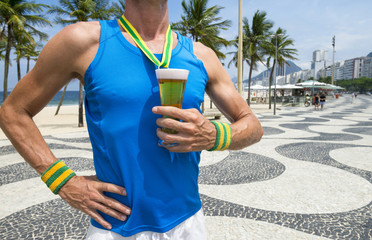 Brazilian athlete standing with first place gold medal in the shape of a glass of beer standing on Copacabana Beach in Rio de Janeiro Brazil