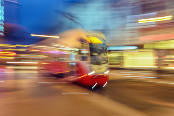 Red tram on urban city street with motion blur effect.