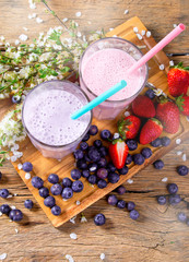 Fresh milk, strawberry, blueberry drinks on wooden table, assorted protein cocktails with fresh fruits.