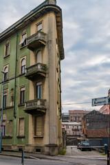 Old narrow house gray-green in the city of Novara. Italy.