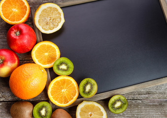 Fresh fruits oranges, kiwi, lemons, apples arranged in a group, natural still life for healthy food. Top view. Empty space for text.
