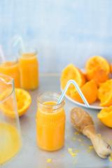 Freshly squeezed orange juice in jar with drinking straw on metallic countertop. Selective focus.