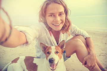 pretty young woman doing selfie with her dog on the beach at sun